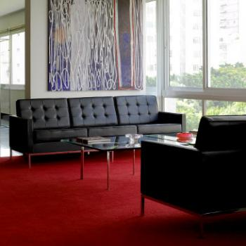 2 black Florence Knoll sofas on a red carpet with a glass coffee table