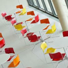 Room with yellow, orange and red 40/4 conference chairs and white tables