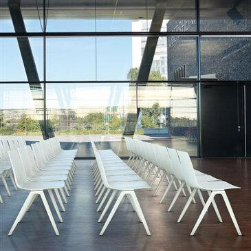Rows of white A-Chairs by large glass window