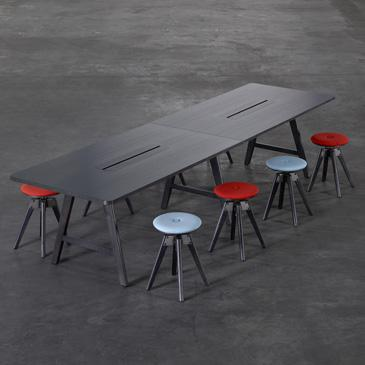 Large A-series table with black stain surrounded by colour chairs