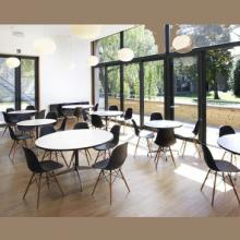 6 round white tables each surrounded by 4 black chairs in a large room with a glass wall to the left